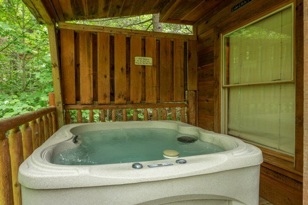 Hot tub and privacy fence on the deck at Logan's Smoky Den, a 2 bedroom cabin rental located in Pigeon Forge