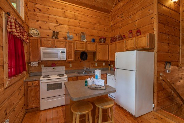 Kitchen with white appliances and breakfast bar with seating for two at Logan's Smoky Den, a 2 bedroom cabin rental located in Pigeon Forge