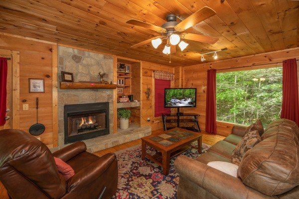 Fireplace, TV, and large picture window in the living room at Logan's Smoky Den, a 2 bedroom cabin rental located in Pigeon Forge
