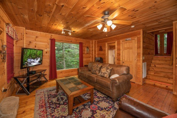 TV, picture window, and sofa in the living room at Logan's Smoky Den, a 2 bedroom cabin rental located in Pigeon Forge