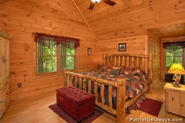 King-sized log bed in a vaulted room at Bear Creek, a 4-bedroom cabin rental located in Pigeon Forge