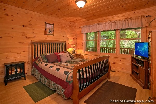 First bedroom with a wooden bed at Bear Creek, a 4-bedroom cabin rental located in Pigeon Forge