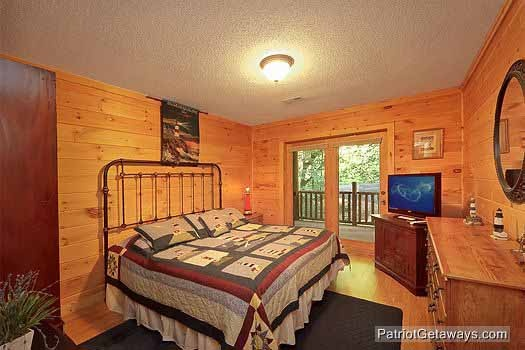 first floor bedroom with king sized bed with french doors out to deck at bear creek a 4 bedroom cabin rental located in pigeon forge