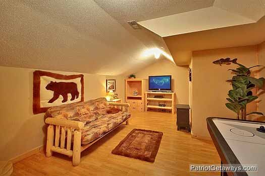 futon by entertainment center and air hockey table on first floor of bear creek a 4 bedroom cabin rental located in pigeon forge