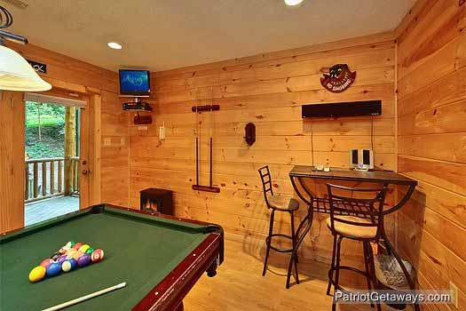 bistro table and chairs with tv mounted in corner of game room at bear creek a 4 bedroom cabin rental located in pigeon forge