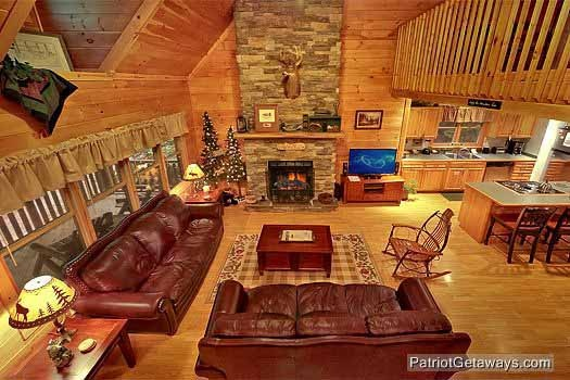 living room with two sofas and a stone fireplace at bear creek a 4 bedroom cabin rental located in pigeon forge