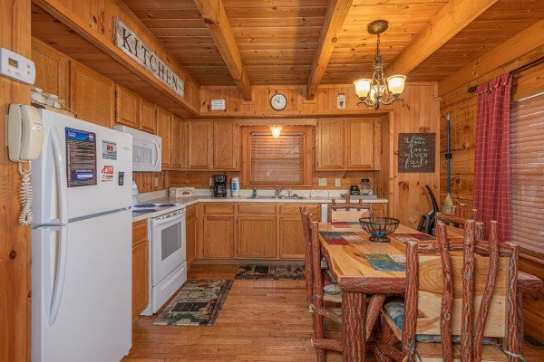 Kitchen with white appliances and dining table for four at Bear Cavern, a 1-bedroom cabin rental located in Pigeon Forge