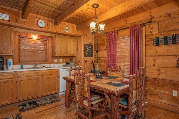 Dining table for four in a kitchen with white appliances at Bear Cavern, a 1-bedroom cabin rental located in Pigeon Forge