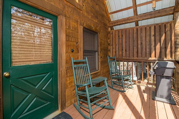 Covered porch with two rocking chairs and a grill at Bear Cavern, a 1-bedroom cabin rental located in Pigeon Forge