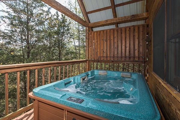 Hot tub on a covered deck with privacy fence at Bear Cavern, a 1-bedroom cabin rental located in Pigeon Forge