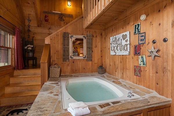 Jacuzzi in the living room at Bear Cavern, a 1-bedroom cabin rental located in Pigeon Forge