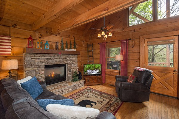 Living room with stone fireplace at Bear Cavern, a 1-bedroom cabin rental located in Pigeon Forge