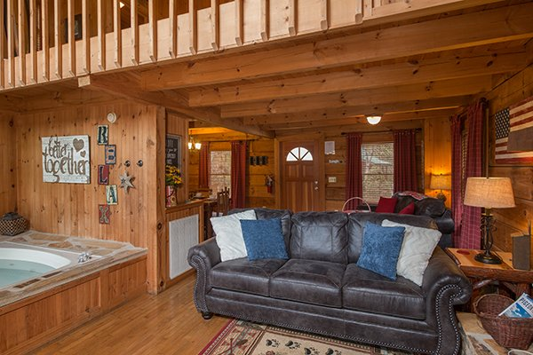 Jacuzzi and sofa at Bear Cavern, a 1-bedroom cabin rental located in Pigeon Forge