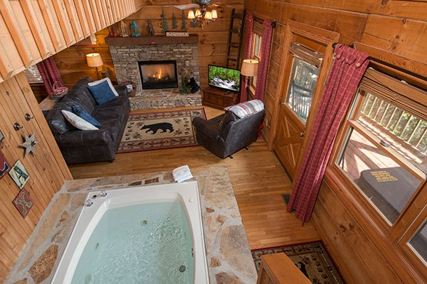 View of the living room jacuzzi and fireplace at Bear Cavern, a 1-bedroom cabin rental located in Pigeon Forge