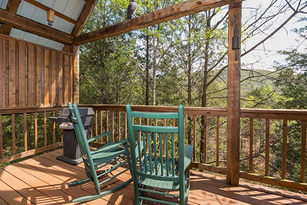 Rocking chairs on a covered deck at Bear Cavern, a 1-bedroom cabin rental located in Pigeon Forge