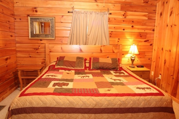 king bed in bedroom at just hanging out a 3 bedroom cabin rental located in pigeon forge
