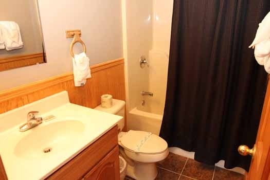 first floor bathroom with tub and shower combination at just hanging out a 3 bedroom cabin rental located in pigeon forge