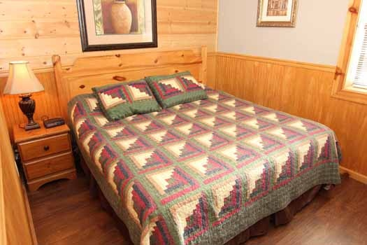 first floor king bed in bedroom on the first floor at just hanging out a 3 bedroom cabin rental located in pigeon forge