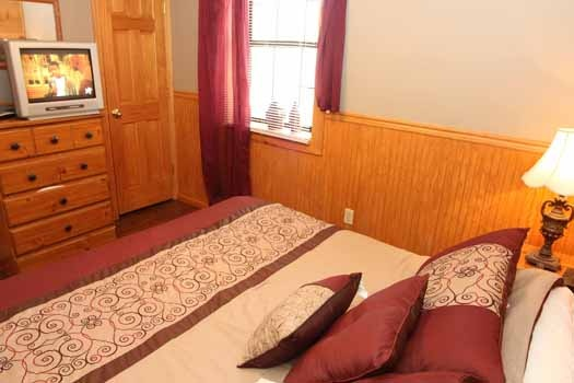 first floor bedroom with tv on chest of drawers at just hanging out a 3 bedroom cabin rental located in pigeon forge