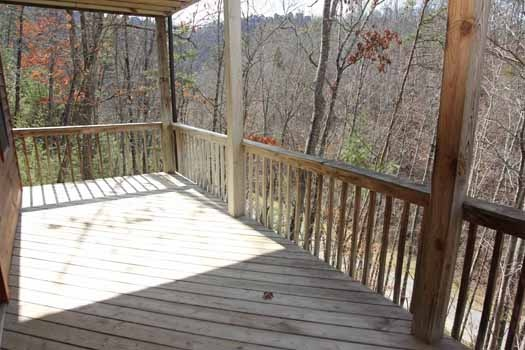 view the mountains through the trees from the deck at just hanging out a 3 bedroom cabin rental located in pigeon forge