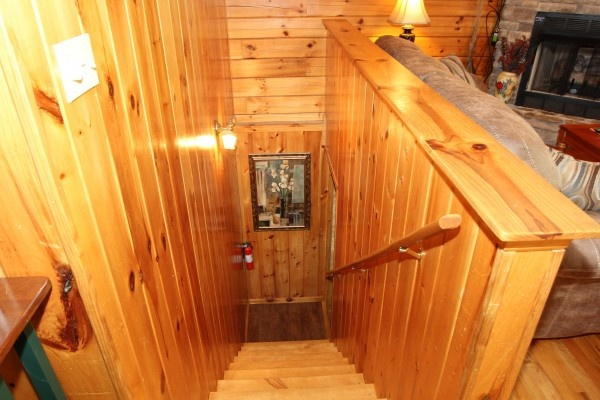 stairs down to first floor at just hanging out a 3 bedroom cabin rental located in pigeon forge
