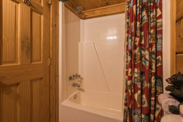 Bathroom with a tub and shower at Boogie Bear, a 1-bedroom cabin rental located in Gatlinburg
