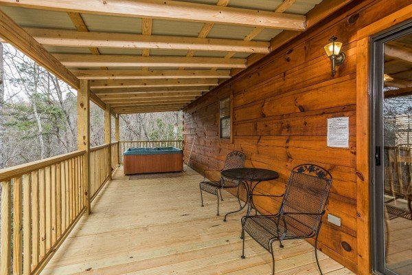 Bistro set for two and a hot tub on a covered deck at Boogie Bear, a 1-bedroom cabin rental located in Gatlinburg