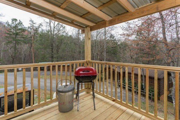 Charcoal grill on a covered deck at Boogie Bear, a 1-bedroom cabin rental located in Gatlinburg