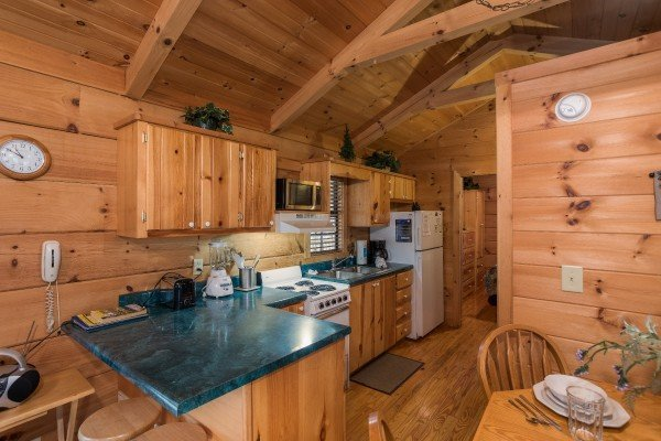 Looking into the kitchen with white appliances from the dining space at Boogie Bear, a 1-bedroom cabin rental located in Gatlinburg