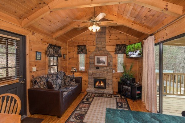 Stone fireplace, TV, and sofa in the living room at Boogie Bear, a 1-bedroom cabin rental located in Gatlinburg
