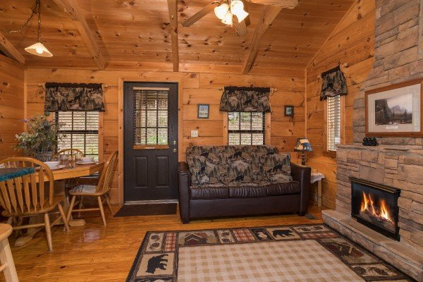 Sofa, fireplace, and dining table in the living space at Boogie Bear, a 1-bedroom cabin rental located in Gatlinburg