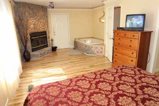 king sized bed in bedroom with fireplace and jacuzzi tub at knotty & nice a 1 bedroom cabin rental located in gatlinburg