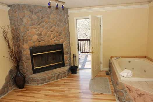 stone fireplace next to jacuzzi tub at knotty & nice a 1 bedroom cabin rental located in gatlinburg