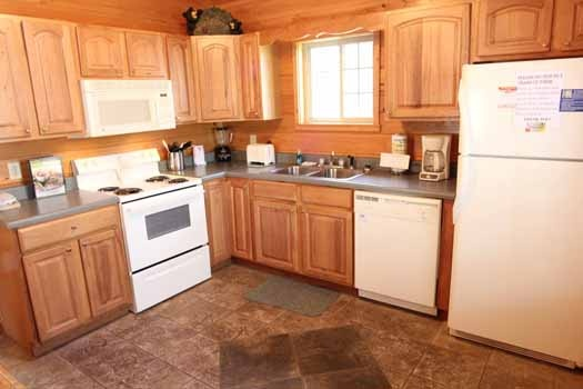 kitchen with white appliances at knotty & nice a 1 bedroom cabin rental located in gatlinburg