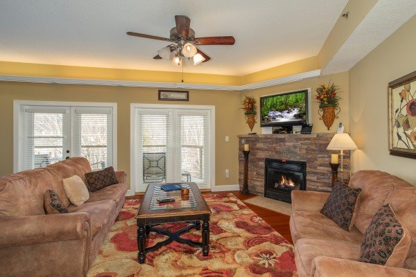 Living room with sofa, loveseat, TV, and fireplace at Heart of Gatlinburg, a 2 bedroom cabin rental located in Gatlinburg
