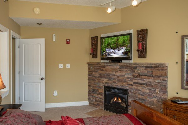 Fireplace and TV in the master bedroom at Heart of Gatlinburg, a 2 bedroom cabin rental located in Gatlinburg