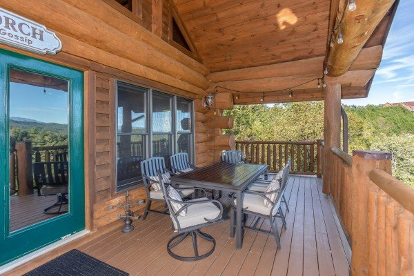 Outdoor dining set with seating for six on the covered deck at Great View Lodge, a 5-bedroom cabin rental located in Pigeon Forge