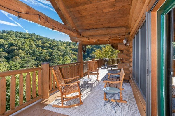 Outdoor seating with string lighting on the covered deck at Great View Lodge, a 5-bedroom cabin rental located in Pigeon Forge