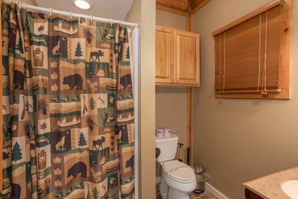 Bathroom with a tub and shower off the game room at Great View Lodge, a 5-bedroom cabin rental located in Pigeon Forge