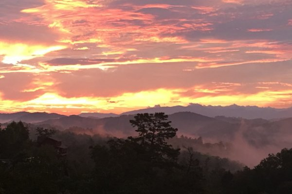 A misty, colorful sunrise from Great View Lodge, a 5-bedroom cabin rental located in Pigeon Forge