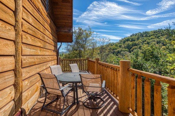 Dining space for four on an open deck at Great View Lodge, a 5-bedroom cabin rental located in Pigeon Forge