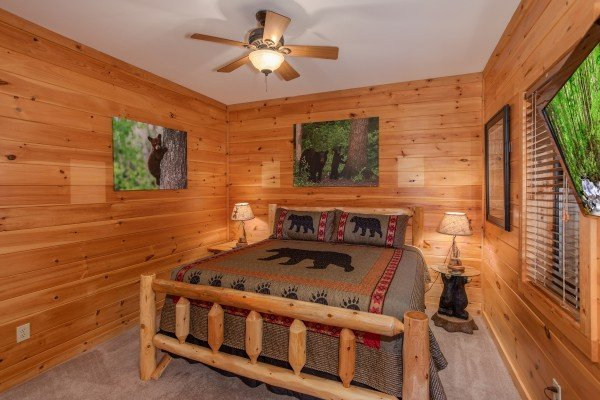 King-sized log bed and two end tables at Great View Lodge, a 5-bedroom cabin rental located in Pigeon Forge