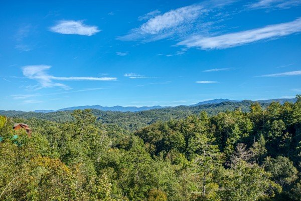 Treetops and mountains viewed from the deck at Great View Lodge, a 5-bedroom cabin rental located in Pigeon Forge