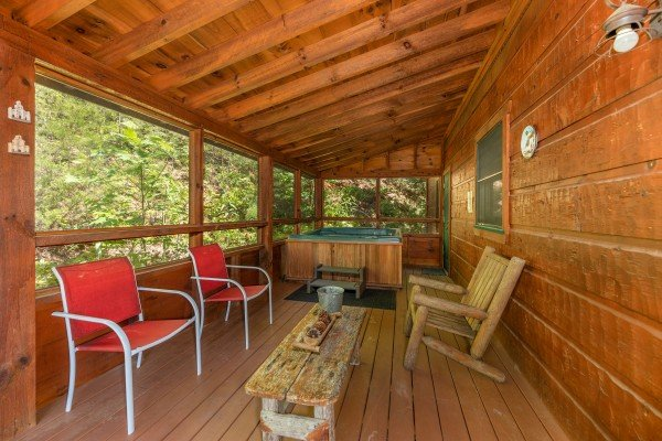 Deck seating and a hot tub on a covered deck at Eagle's Loft, a 2 bedroom cabin rental located in Pigeon Forge