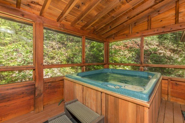 Hot tub on a covered porch at Eagle's Loft, a 2 bedroom cabin rental located in Pigeon Forge