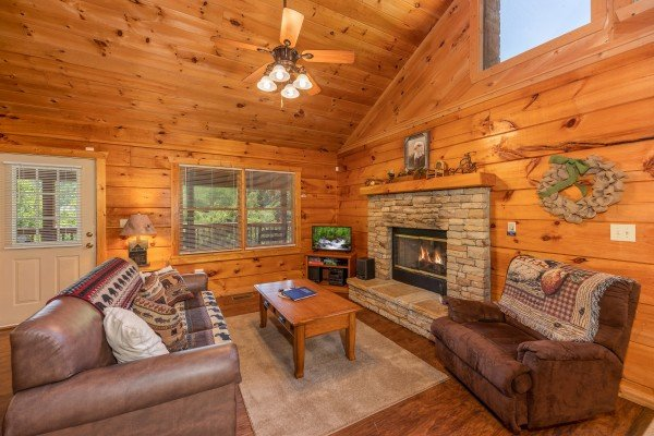 Living room with fireplace and sleeper sofa at Eagle's Loft, a 2 bedroom cabin rental located in Pigeon Forge