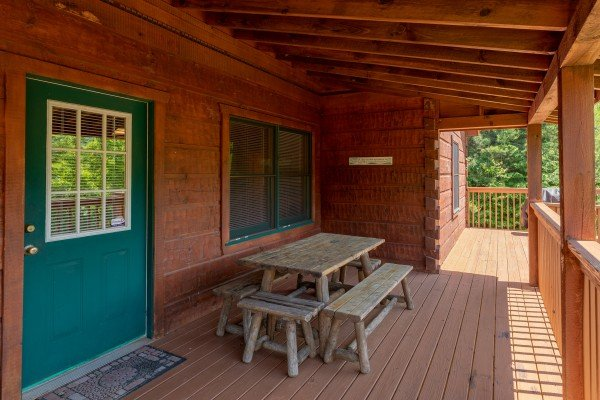 Picnic table on a covered deck at Eagle's Loft, a 2 bedroom cabin rental located in Pigeon Forge