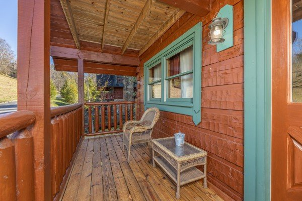Front porch with a wicker chair and table A Beary Nice Cabin, a 2 bedroom cabin rental located in Pigeon Forge