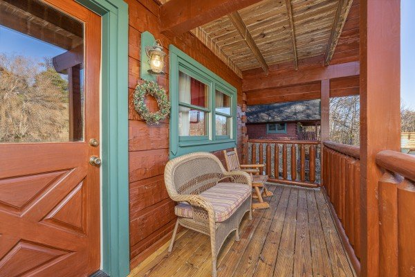 Wicker bench and small rocking chair on the front porch at A Beary Nice Cabin, a 2 bedroom cabin rental located in Pigeon Forge