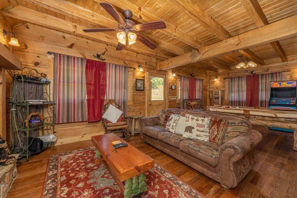 Living room and game room at A Beary Nice Cabin, a 2 bedroom cabin rental located in Pigeon Forge